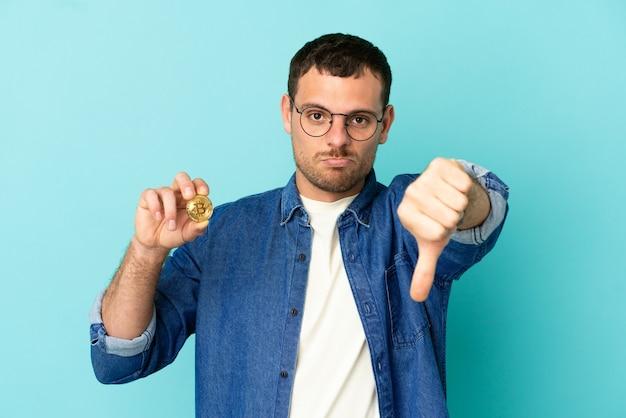 Uomo brasiliano che tiene un bitcoin su sfondo blu isolato che mostra il pollice verso il basso con espressione negativa