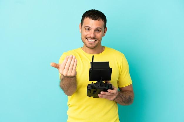 Uomo brasiliano in possesso di un telecomando drone su sfondo blu isolato che invita a venire con la mano. felice che tu sia venuto