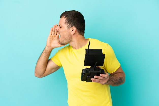 Uomo brasiliano con in mano un telecomando drone su sfondo blu isolato che grida con la bocca spalancata di lato