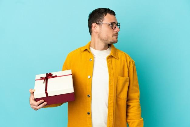 Uomo brasiliano che tiene un regalo su sfondo blu isolato guardando di lato