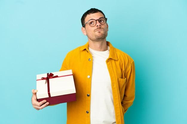Uomo brasiliano che tiene un regalo su sfondo blu isolato e guarda in alto