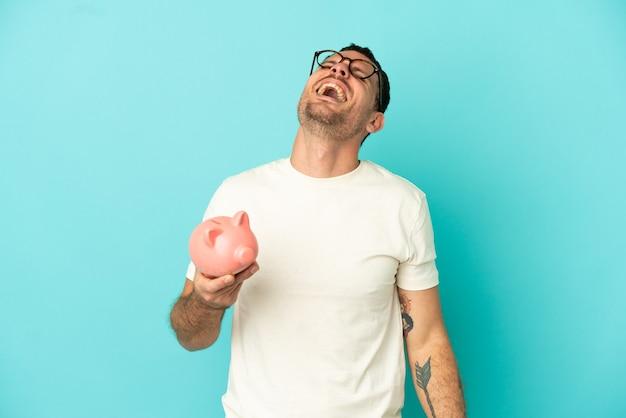 Uomo brasiliano che tiene un salvadanaio su sfondo blu isolato ridendo