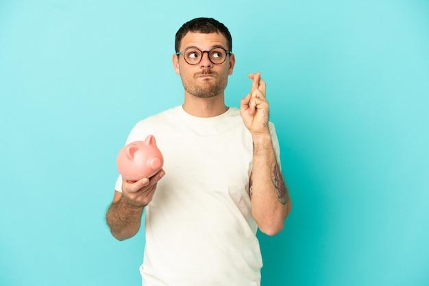 Uomo brasiliano che tiene un salvadanaio su sfondo blu isolato con le dita incrociate e augurando il meglio