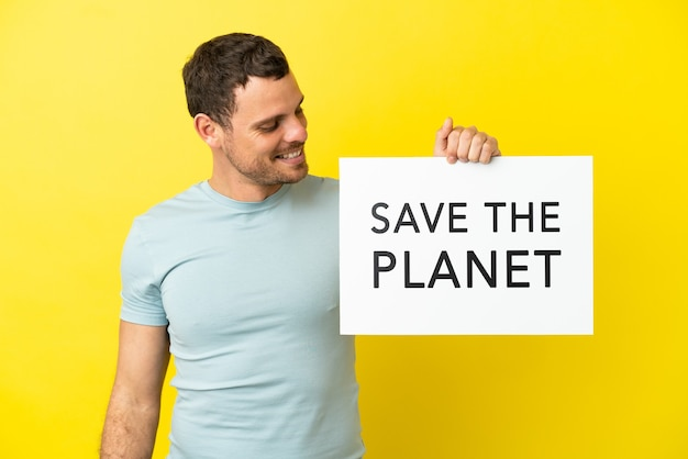 Uomo brasiliano su sfondo viola isolato che tiene un cartello con il testo save the planet