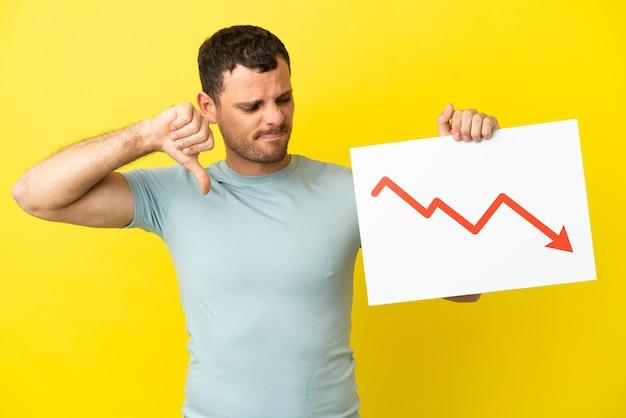 Uomo brasiliano su sfondo viola isolato con un cartello con un simbolo di freccia di statistiche decrescenti e che fa un cattivo segnale