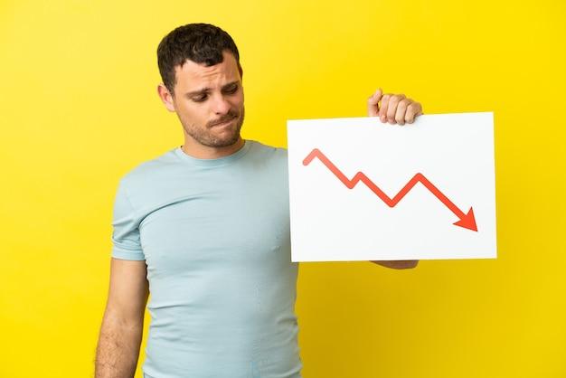 Uomo brasiliano su sfondo viola isolato con un cartello con un simbolo di freccia di statistiche decrescenti con espressione triste