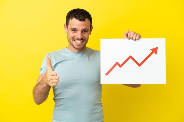 Uomo brasiliano su sfondo viola isolato con un cartello con un simbolo di freccia di statistiche in crescita che fa un affare