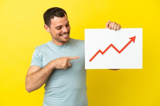 Uomo brasiliano su sfondo viola isolato con un cartello con un simbolo di freccia di statistiche in crescita e puntandolo