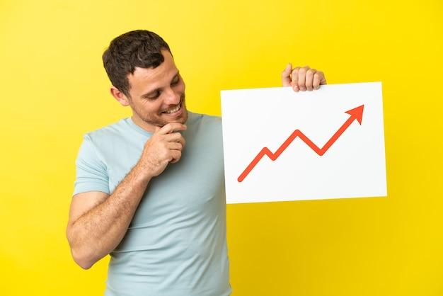 Uomo brasiliano su sfondo viola isolato con un cartello con un simbolo di freccia di statistiche in crescita e pensiero