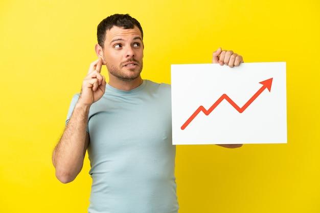 Uomo brasiliano su sfondo viola isolato con un cartello con un simbolo di freccia statistica in crescita con le dita incrociate
