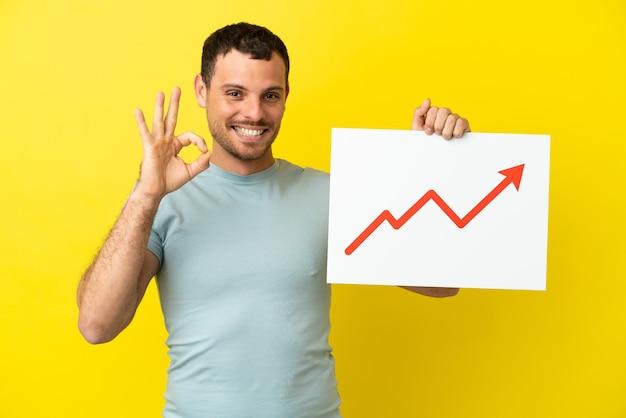 Uomo brasiliano su sfondo viola isolato con un cartello con un simbolo di freccia di statistiche in crescita con segno ok