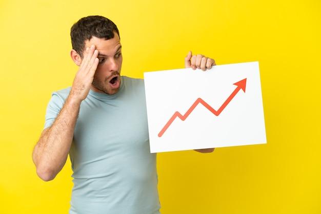 Uomo brasiliano su sfondo viola isolato con un cartello con un simbolo di freccia statistica in crescita con espressione sorpresa