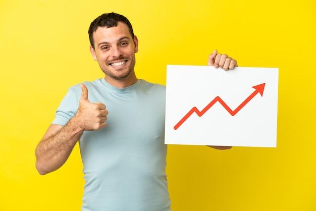 Uomo brasiliano su sfondo viola isolato con un cartello con un simbolo di freccia di statistiche in crescita con il pollice in su