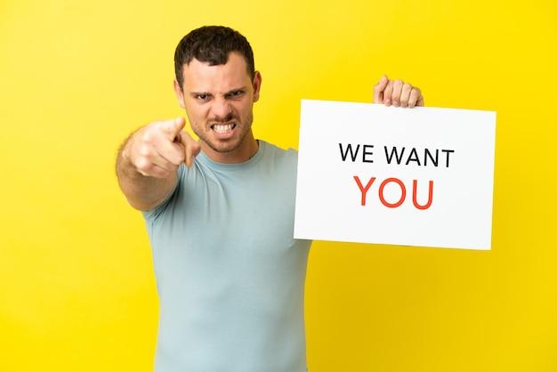 Uomo brasiliano su sfondo viola isolato tenendo we want you board e indicando la parte anteriore
