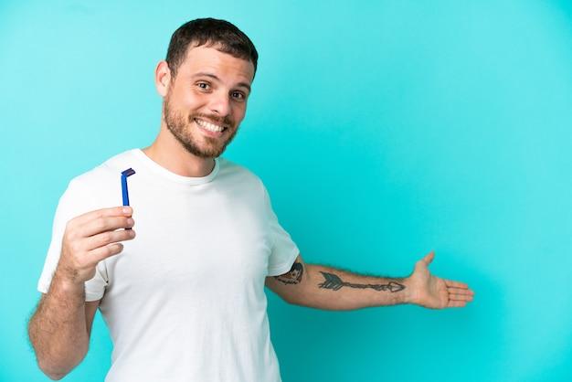 Uomo brasiliano che si rade la barba isolato su sfondo blu allungando le mani di lato per invitare a venire