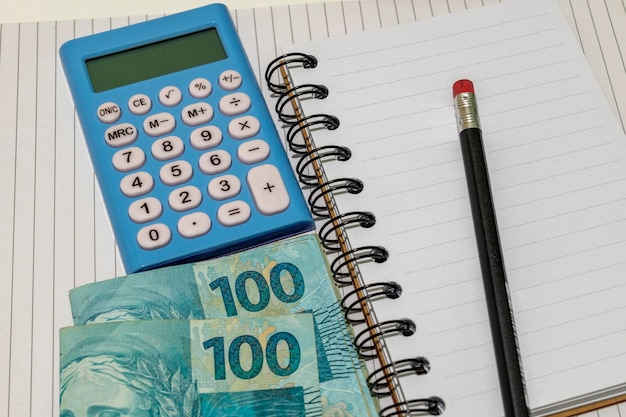 Soldi brasiliani, calcolatrice e blocco note