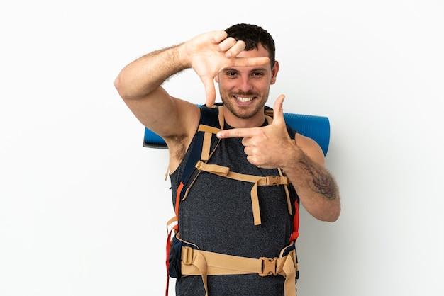 Uomo brasiliano dell'alpinista con un grande zaino sopra fondo bianco isolato che mette a fuoco il fronte. simbolo di inquadratura