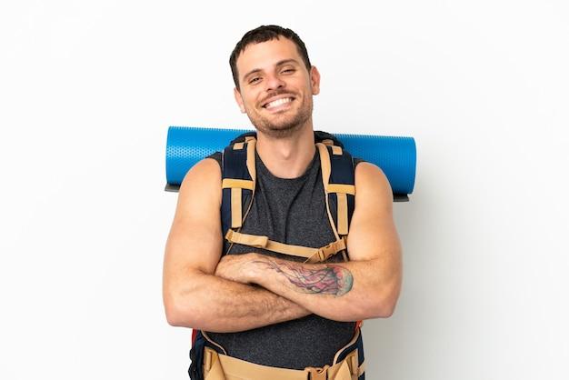 Uomo alpinista brasiliano con un grande zaino su sfondo bianco isolato mantenendo le braccia incrociate in posizione frontale