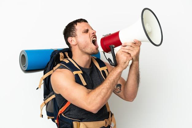 Uomo brasiliano dell'alpinista con un grande zaino sopra fondo bianco isolato che grida tramite un megafono