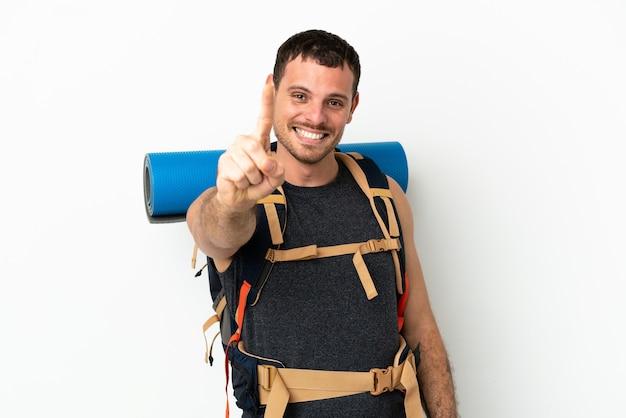Uomo brasiliano dell'alpinista con un grande zaino sopra fondo bianco isolato che mostra e che solleva un dito