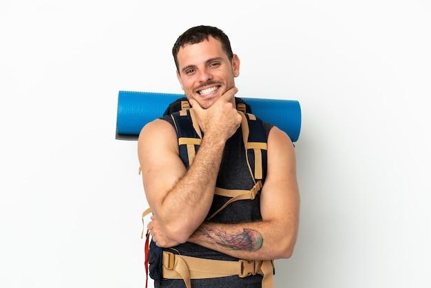 Uomo brasiliano alpinista con un grande zaino su sfondo bianco isolato sorridente