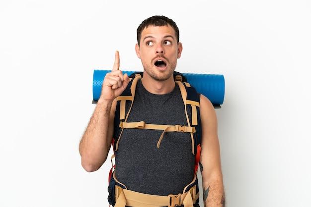 Uomo alpinista brasiliano con un grande zaino su sfondo bianco isolato pensando a un'idea che punta il dito verso l'alto