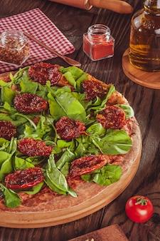 Pizza brasiliana con salsa di pomodoro, mozzarella, rucola, pomodori secchi e origano (pizza de rucula con tomate seco) - primo piano.