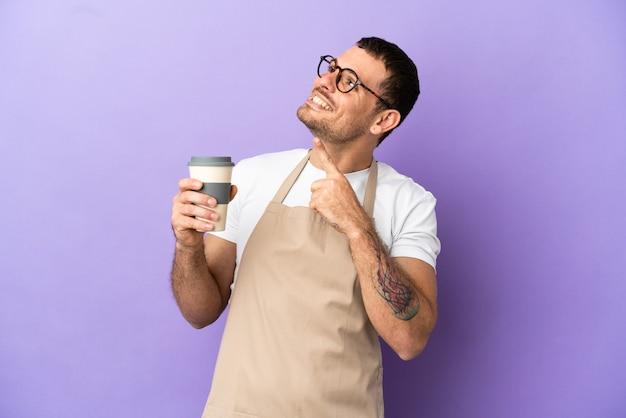 Cameriere brasiliano del ristorante sopra fondo porpora isolato che indica con il dito indice una grande idea