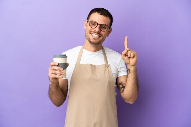 Cameriere brasiliano del ristorante sopra fondo porpora isolato che mostra e che alza un dito nel segno del meglio