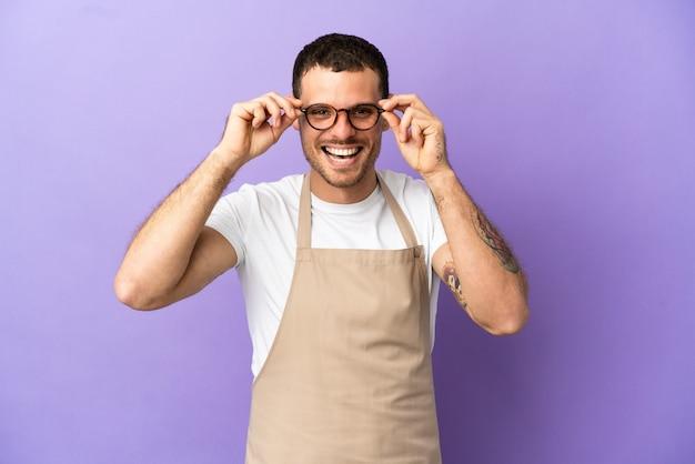 Cameriere brasiliano del ristorante sopra fondo porpora isolato con i vetri e sorpreso