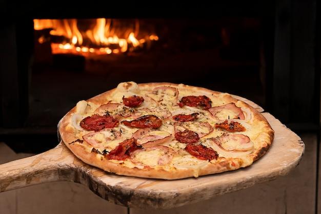 Pizza in stile brasiliano che entra nel forno a legna. messa a fuoco selettiva