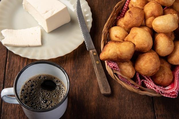 Il dolce brasiliano ha chiamato il bolinho de chuva, in un canestro, formaggio su legno rustico, fuoco selettivo.