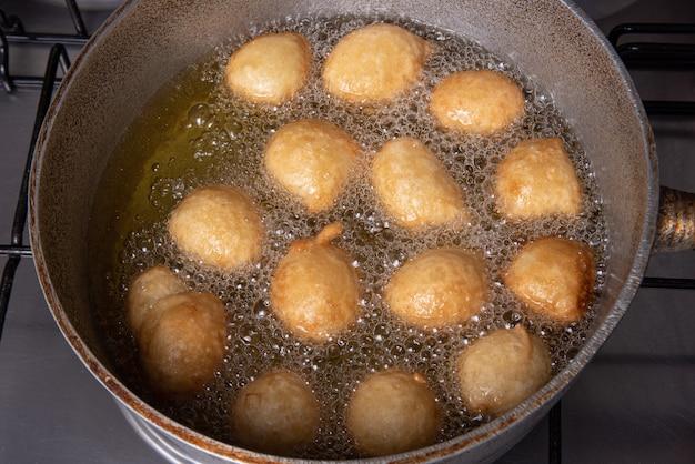 Il dolce brasiliano chiamato bolinho de chuva, fritto in padella con olio, fuoco selettivo.