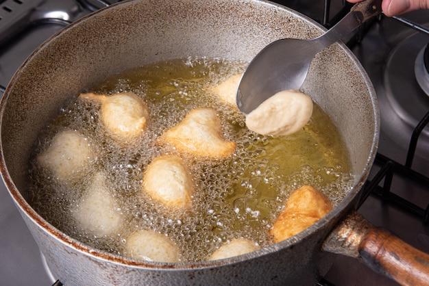 Il dolce brasiliano chiamato bolinho de chuva, messo a friggere in una padella con olio, fuoco selettivo.