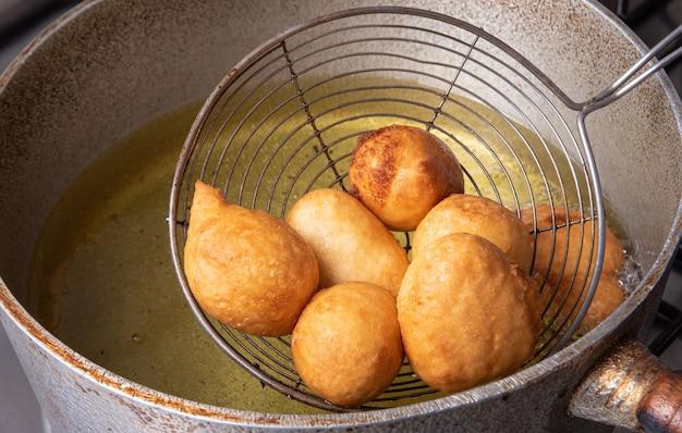 Il dolce brasiliano chiamato bolinho de chuva, preso dalla frittura in padella con olio, fuoco selettivo.