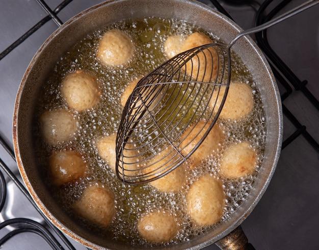 Dolce brasiliano chiamato bolinho de chuva, preso dalla frittura in padella con olio, vista dall'alto.