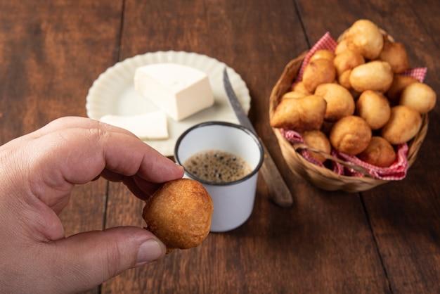 Il dolce brasiliano ha chiamato il bolinho de chuva, il formaggio e una tazza di caffè su legno rustico, fuoco selettivo.