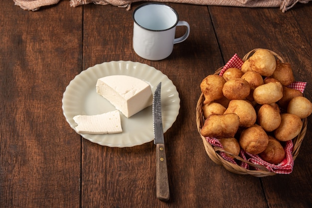 Il dolce brasiliano ha chiamato il bolinho de chuva, disposto in un canestro, formaggio, legno rustico, fuoco selettivo.
