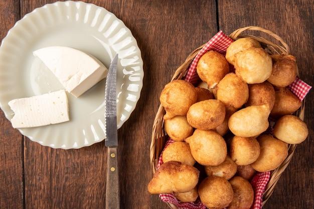 Il dolce brasiliano chiamato bolinho de chuva, posto in un cesto, formaggio su legno rustico, vista dall'alto.