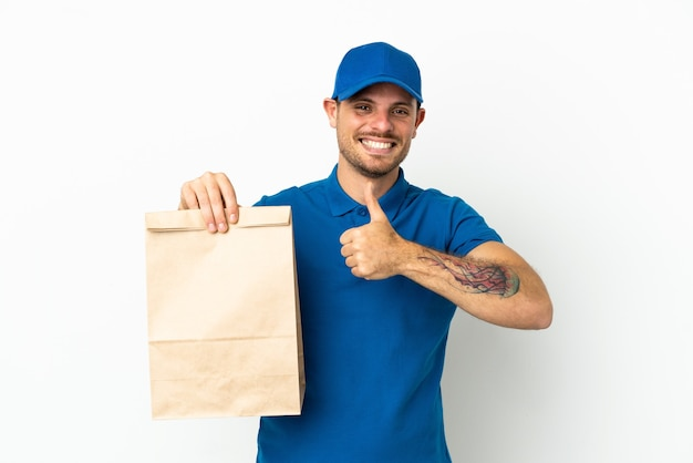Brasiliano che prende un sacchetto di cibo da asporto isolato su sfondo bianco dando un gesto di pollice in alto