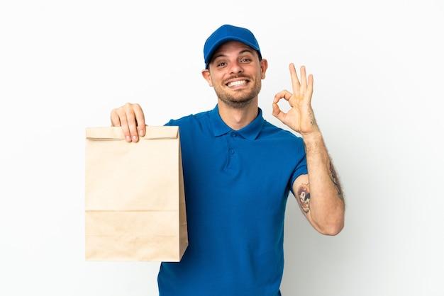 Brasiliano che prende un sacchetto di cibo da asporto isolato su sfondo bianco che mostra segno ok con le dita