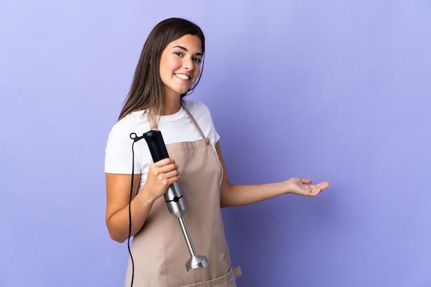 Donna brasiliana che utilizza un frullatore a immersione isolato sulla parete viola che estende le mani a lato per invitare a venire