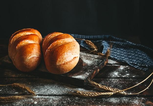 Pane cotto su un tavolo rustico fatto di farina e spighe di grano