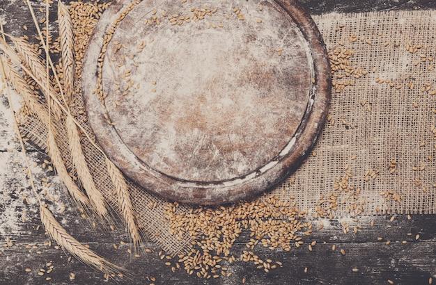 Sfondo di cottura del pane. grano e spighe sparsi su legno rustico vicino allo scrittorio di legno rotondo cosparso di farina. raccolta del grano agricolo, composizione per la panificazione