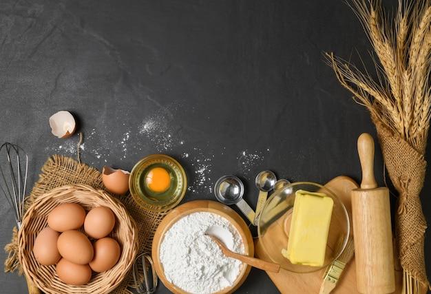 Farina di pane con uova fresche, burro non salato e accessori da forno su fondo di legno, preparati per il concetto di panetteria fatta in casa