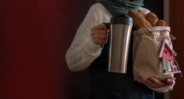 Mano del pane che tiene caffè bianco di consegna del sacchetto della spesa di natale di nuovo anno per andare