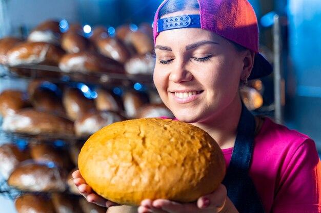 Pane nelle mani di un fornaio. cottura calda dal forno. produzione industriale di pane. mani di panettiere con pane