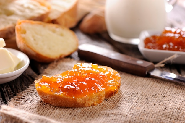 Pane e marmellata fatta in casa di arance sul tavolo di legno