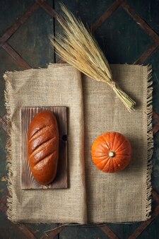 Pane, zucca, grano, tela da imballaggio giacciono su un vecchio serpente
