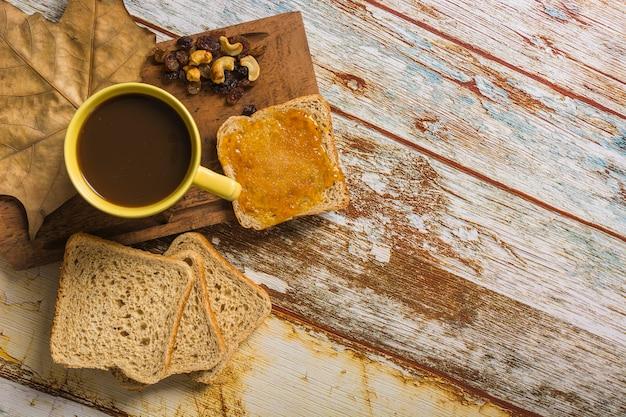 Pane e uvetta vicino a caffè e foglie